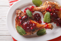 Tasty baked duck leg with cranberry sauce and mint closeup on a Stock Photos