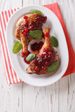 Tasty baked duck leg with cranberry sauce and mint closeup on a Stock Photo