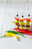 Tasty banderillas with peppers, olives and anchovies for spanish corrida. On white table Stock Photo