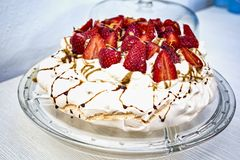 Tasty and beautiful meringue cake decorated with red strawberries cut in half and decorated with liquid caramel. Meringue cake with red strawberry ornament cut royalty free stock images
