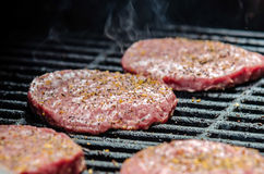 Tasty beef burgers on the grill Royalty Free Stock Photography