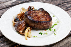 Tasty Beef Mignon steak with mushrooms and herbs on plate. Tasty Beef Mignon steak with mushrooms and herbs on plate royalty free stock photo