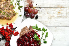 Tasty beef and pork meat dishes garnished with cherry and grapes Stock Images