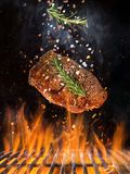 Tasty beef steak flying above cast iron grate with fire flames. Freeze motion barbecue concept stock photo