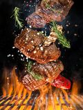Tasty beef steak flying above cast iron grate with fire flames. Freeze motion barbecue concept royalty free stock photography