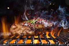 Beef steak on the grill with flames. Tasty Beef steak on the grill with fire flames royalty free stock photos