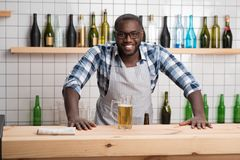 Positive barman standing at the bar counter and smiling cheerfully. Tasty beer. Friendly emotional handsome barman standing with his hands on a bar counter and Stock Image