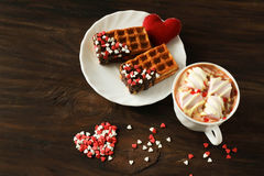 Tasty Belgian waffle with hot chocolate. Tasty Belgian waffle with berries, cream and heart shaped topping and hot chocolate with marshmallows for breakfast on Royalty Free Stock Photography
