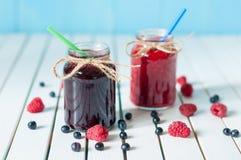 Tasty berries jam in mason jar on light wooden Royalty Free Stock Images