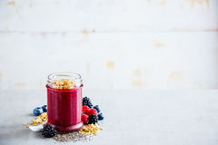 Tasty berry smoothie. Close up of berry smoothie with fresh berries and chia seeds in glass jar, white wooden wall background, copy space, selective focus. Clean stock image