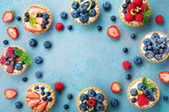 Tasty berry tartlets or cake with cream cheese and different berries around. Pastry dessert top view. Tasty berry tartlets or cake with cream cheese and stock photos