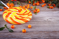Tasty big striped lollipop on the wooden background Royalty Free Stock Photos