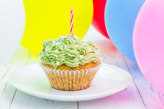 Tasty birthday cupcake with candle, colorful balloons on background Royalty Free Stock Images