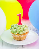 Tasty birthday cupcake with candle, colorful balloons on background Stock Images