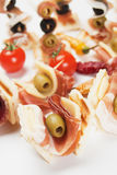 Tasty bites with prosciutto and olives Stock Photo