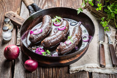 Tasty black pudding with onion and parsley Stock Photos