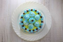 Tasty blue cake decorated with whipped cream and chocolate balls on a white plate stock photo