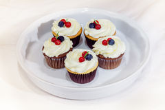 Tasty blueberry cupcakes decorated with cream and fresh berries Stock Photo