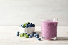 Tasty blueberry smoothie in glass, bowl royalty free stock images