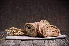 Tasty bread with wheat on wooden background. Stock Image