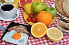 Tasty breakfast or brunch. Breakfast or brunch with cup of fresh coffee, ham and eggs, cereals, bread and fruits served on red-white tablecloth Stock Photos