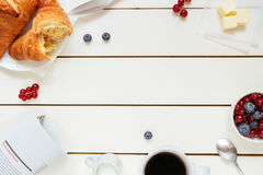 Tasty breakfast with coffee, berries, croissant on the white wooden table with copy space, top view Royalty Free Stock Photos
