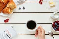 Tasty breakfast with coffee, berries, croissant on the white wooden table, top view.  Stock Photos