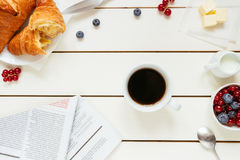 Tasty breakfast with coffee, berries, croissant on the white wooden table, top view.  Royalty Free Stock Photo