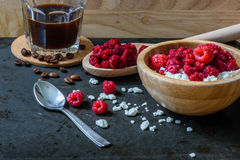 Tasty breakfast with cottage cheese, raspberries and cup of coffee. Scattered berries and grains of curd Royalty Free Stock Photography