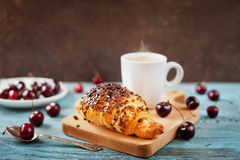 Tasty breakfast with fresh croissant, coffee and cherries on a wooden table Royalty Free Stock Photography