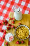 Tasty breakfast, fresh milk in glass bottle, cereals with honey and nuts in green ceramic bowl, tasty yogurt royalty free stock image