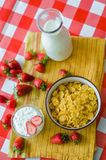 Tasty breakfast, fresh milk in glass bottle, cereals with honey and nuts in green ceramic bowl, tasty yogurt, top view stock photo