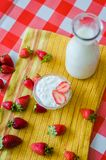 Tasty breakfast, fresh milk in glass bottle, tasty yogurt in small glass bowl with a lot of strawberries around stock image