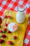 Tasty breakfast, fresh milk in glass bottle, tasty yogurt in small glass bowl with a lot of strawberries around stock photo