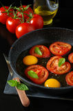 Tasty breakfast : fried eggs with tomatoes, cooking Stock Photography