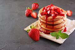 Tasty breakfast. Homemade pancakes and berry syrup with fresh strawberry Royalty Free Stock Image