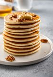 Tasty breakfast. Homemade pancakes with crushed walnut, honey or maple syrup on grey background. Tasty breakfast. Homemade pancakes with crushed hazelnut, honey stock photo