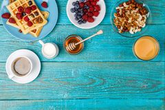 Homemade waffles, fresh raspberries and blueberry, cup of coffee, milk, nuts and honey. Tasty breakfast - homemade waffles, fresh raspberries and blueberry, cup Royalty Free Stock Photo