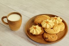 Tasty breakfast. Hot milk in clay cup and fragrant crumbly cookies with raisins nuts and jam on ceramic plate on light brown woode stock images