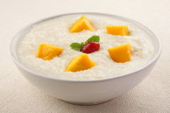 Tasty  Breakfast . - Organic rice pudding with yellow mango and coconut. Mango rice pudding. Royalty Free Stock Photography
