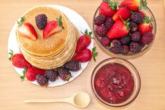 Tasty breakfast. Pancakes with fruit, strawberries and blackberries mora, poured syrup honey on a wooden tray. vector illustration