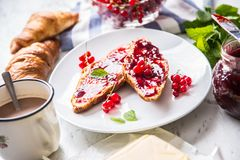 Tasty breakfast with red currants marmalade croissants butter an. D mint leaves stock photos