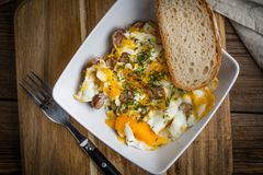 Scrambled eggs with sausage and bread. Tasty breakfast - scrambled eggs with sausage and bread Royalty Free Stock Photo