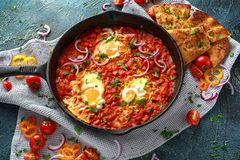 Tasty Breakfast Shakshuka in a Iron Pan. Fried eggs with tomatoes, red, yellow peppers, onion, parsley, Pita bread and Royalty Free Stock Image