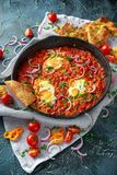 Tasty Breakfast Shakshuka in a Iron Pan. Fried eggs with tomatoes, red, yellow peppers, onion, parsley, Pita bread and Stock Images