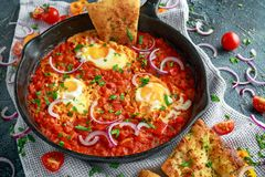 Tasty Breakfast Shakshuka in a Iron Pan. Fried eggs with tomatoes, red, yellow peppers, onion, parsley, Pita bread and Stock Photos