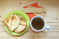 Tasty breakfast top view. Two sandwiches, crispbread and cup of tea on a wooden table Royalty Free Stock Photos