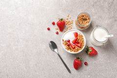 Tasty breakfast with yogurt, berries and granola. On gray table, top view Stock Photography