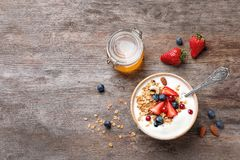 Tasty breakfast with yogurt, berries and granola. On wooden table, top view Stock Images