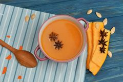 Tasty bright soup of pumpkin puree. In a beautiful dish with seeds and anise on a wooden background Royalty Free Stock Image